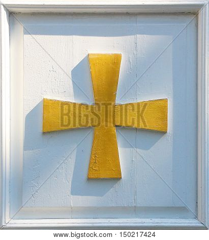 Gold painted wooden cross adorning the door of a church building in late afternoon