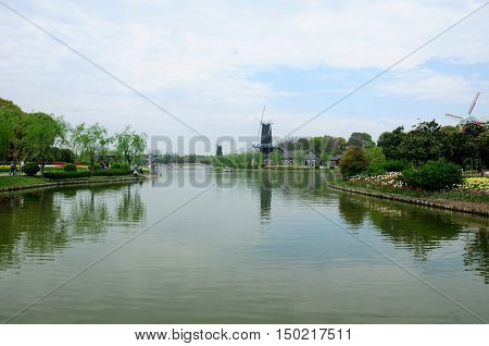 A small manmade lake at the shanghai flower port surrounded by windmills trees and gardens on a cloudy spring day in China.
