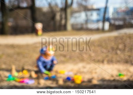 Small lone child playing in the sandbox. The blurring