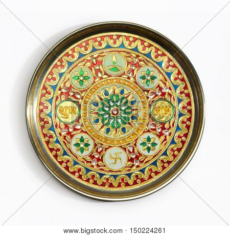 An isolated Indian pooja thali- a decorative plate with intricate hindu religious design and motifs.