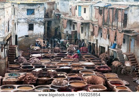 FEZ, MOROCCO - JANUARY 4, 2014: Workers in the tannery souk of weavers in Fez, Morocco. The tannery souk of weavers is the most visited part of the 2000 years old city.