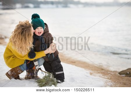 Portrait of young woman hugging her adorable little toddler boy on a winter cold day. Mother and child walking by river and having fun. Happy family outdoors. Winter Christmas and lifestyle concept