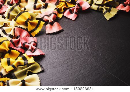 Farfalle tigrate pasta forming frame on dark stone background. Place for text. Concept of slow carbohydrates for healthy nutrithion.