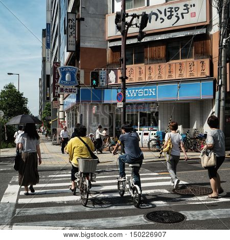 Osaka - June 2016: Street view with people on crosswalk in sunny day