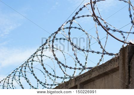 The broad line of barbed wire fence on sky background.