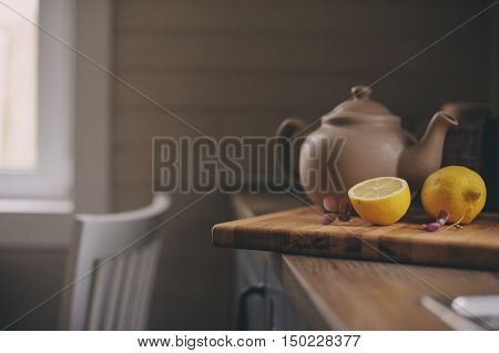 Tea pot and lemons in rustic grey kitchen interior. Slow living in country house concept. Cozy morning at home
