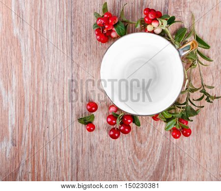 red lingonberries and top viewed empty coffee cup on wooden background