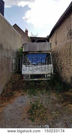 Old destroyed transport van standing between buildings.