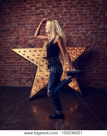 Happy Trendy Teen Girl Dancing And Jumping On Yellow Star And Brick Wall Background. Toned Contrast