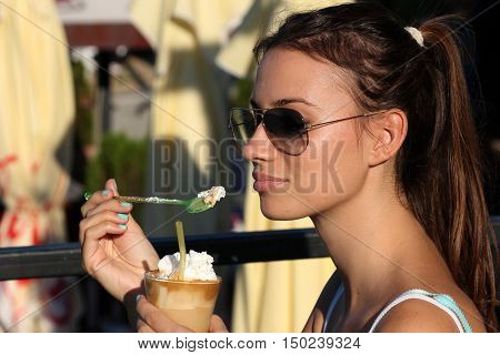 Girl drink coffee with cream in the bar