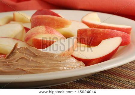 Close-up of freshly sliced apples and peanut butter on plate with color coordinated napkin as background.  Shallow dof