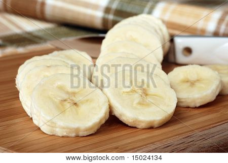 Banana slices on wooden cutting board with knife and plaid table linen in the background.  Macro still-life with shallow dof