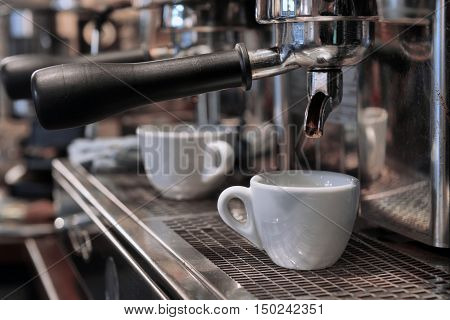 Espresso pouring into a cup on a bar