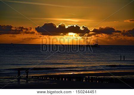 Sunset on the beach and ship on the ocean in Vlissingen, Nederland