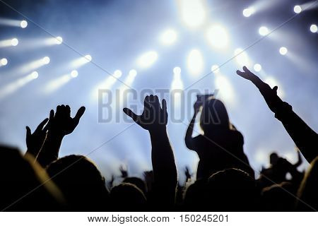 People silhouettes of concert crowd in front of bright stage white and blue lights