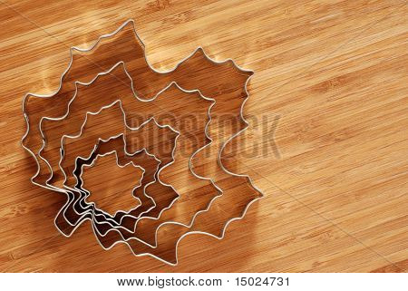 Set of leaf cookie cutters on bamboo cutting board.  Natural sunlight reflecting off metal.