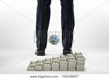 Close-up legs with packs of dollars and small model of globe. Human impact on the environment. Consumption of natural resources. Business and finance. Elements of this image are furnished by NASA