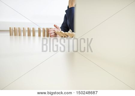 Businesswoman interrupting a falling domino effect inserting her hand into the line to prevent a further domino from falling in a conceptual image cropped view with copy space.