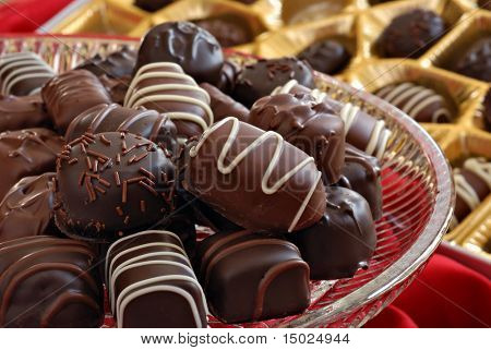 Assorted chocolate candies on crystal serving plate with boxed candy in background.  Macro with shallow dof