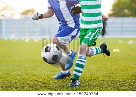 Sports education. Football training for children. Soccer players kicking soccer ball on sports venue. European football competition between two teams