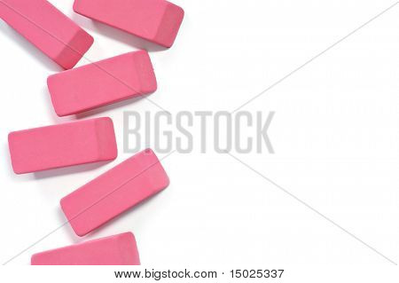 Classic pink erasers on white background with copy space.