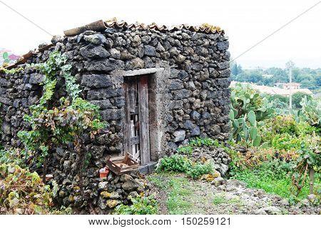 Cascina di campagna con porta di legno, tegole e orto