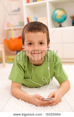 Happy Boy Listening To Music Laying On The Floor