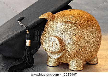 Higher education conceptual image of gold piggy bank with graduation cap on reflective surface.  Macro with shallow dof.  Focus on the bank.
