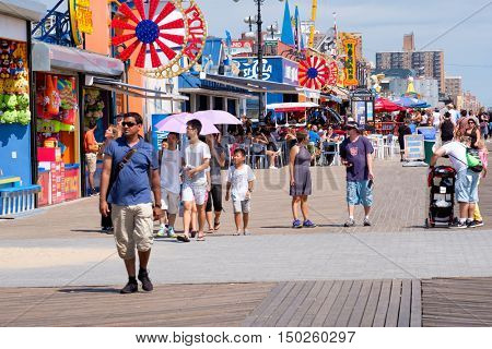NEW YORK,USA - AUGUST 18,2016 : People and colorful food stands at the seaside boardwalk at Coney Island in New York City
