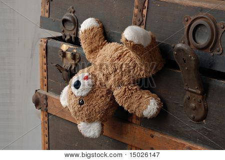 Shabby old abandoned teddy bear in  rustic antique steamer trunk.  Close-up with shallow dof.