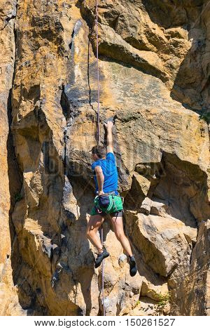 Male rock climber climbing up a cliff, hanging and holding one hand in the chalk bag
