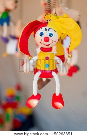 Colorful wooden buffoon figure / toy hanging on the spring