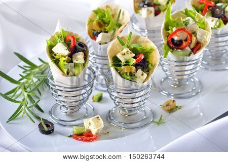 Mini tortillas stuffed with Greek farmers salad with feta cheese and olives, served in wire egg cups