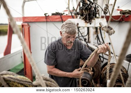BEAUFORT, SOUTH CAROLINA-OCTOBER 16, 2015: Unidentified worker handles rigging on a fishing vessel off the coast of Beaufort, South Carolina.
