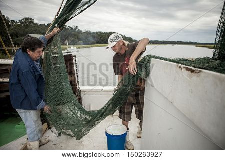 BEAUFORT, SOUTH CAROLINA-OCTOBER 16, 2015: Unidentified workers haul nets  on a fishing vessel off the coast of Beaufort, South Carolina