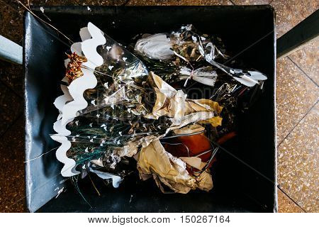 Bouquet Of Wilted Flowers In A Wastebasket