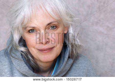 Retrato casual de mujer madura feliz con pelo blanco natural y maquillaje mínimo.
