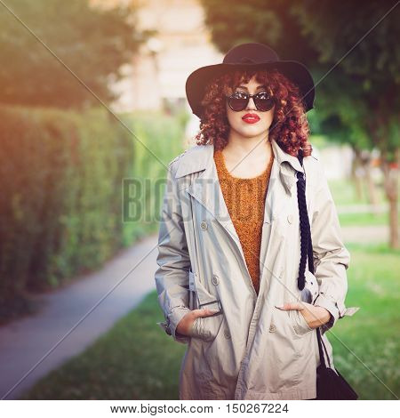 Modern stylish young woman in park in autumn. Closeup portrait of beautiful female person, in trench coat, floppy hat fall outfit standing in park. Retouched, filter applied, natural light.
