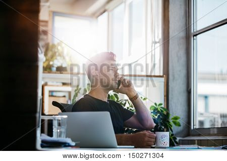 Businessman At His Desk Talking On Mobile Phone