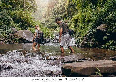 Couple Walking Across The Stream.