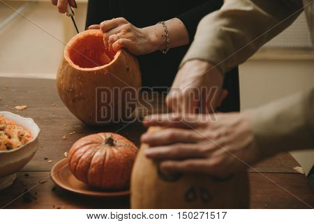 man and woman hands curving pumpkin preparing for Halloween