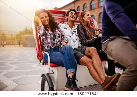 Teenage friends enjoying tricycle ride in the city. Teenagers riding on tricycle on road and smiling.