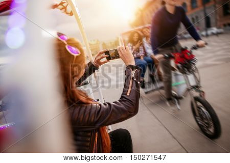 Woman photographing friends riding tricycle on road. Young people on tricycle on city street.