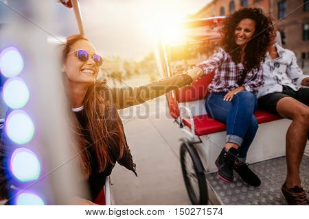 Best friends enjoying tricycle ride in the city. Teenage girls riding on tricycles and holding hands.
