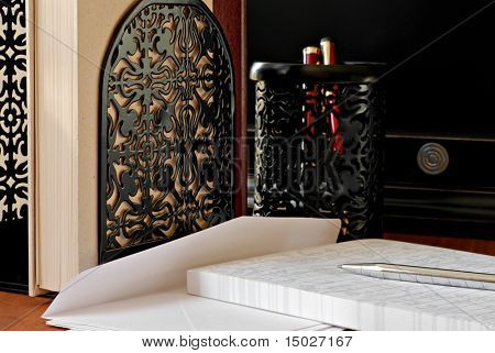 Classic letter writing still life with decorative bookends and pen holder in background.  Closeup with shallow dof.