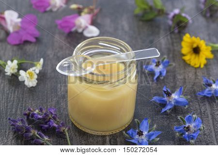 raw organic royal jelly in a small bottle on slate board