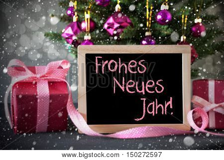 Chalkboard With German Text Frohes Neues Jahr Means Happy New Year. Christmas Tree With Rose Quartz Balls, Snowflakes And Bokeh Effect. Gifts Or Presents In The Front Of Cement Background.