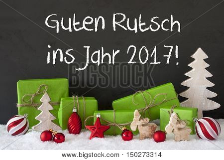 German Text Guten Rutsch Ins Jahr 2017 Means Happy New Year 2017. Green Gifts With Christmas Decoration Like Tree, Moose Or Red Christmas Tree Ball. Black Cement Wall As Background With Snow.