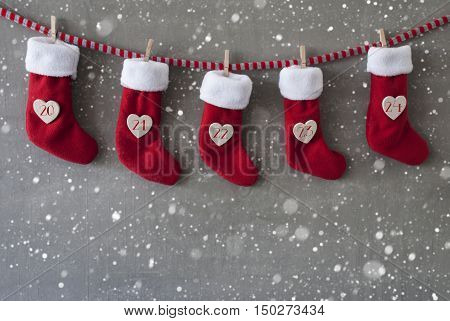Nicholas Boots As Advent Calendar Hanging On A Line. Cement Wall As Modern Background With Snowflakes. Textile Shoes With Hearts With Numbers 20 Till 24 For Christmas Eve
