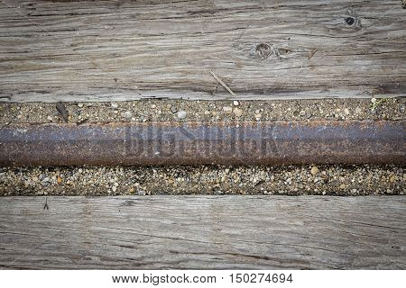 horizontal background image of an old wood surface with an iron railroad tie going through the middle great for text or copy space.